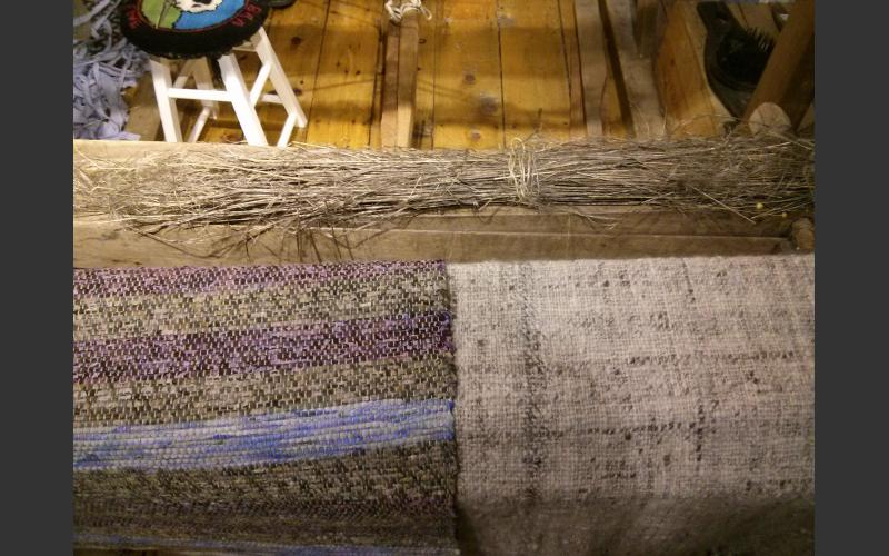 Unprocessed flax, and two mats weaved using the loom.