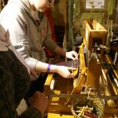 Teaching visitors how to use the smaller loom, used for smaller projects.